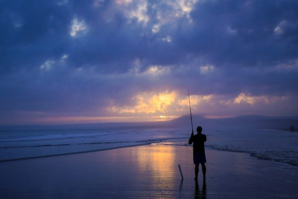Angler fishing on beach
