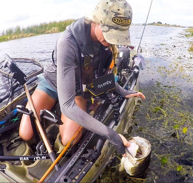 Female Angler Lands Largemouth Bass in Kayak