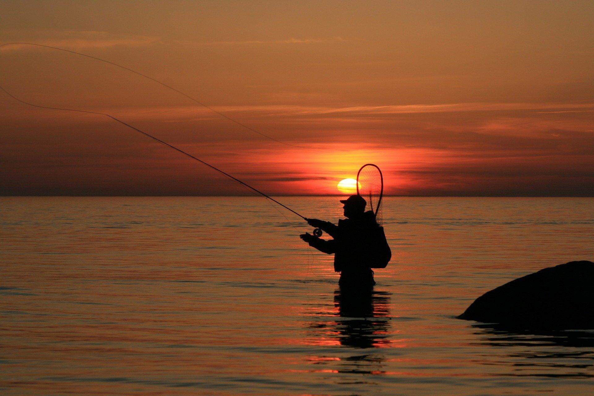 Angler fishing in sunset
