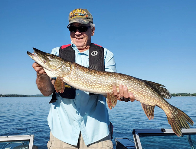 Military veteran holds large northern pike