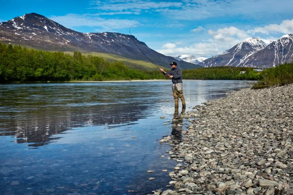 Angler fly fishing in mountains